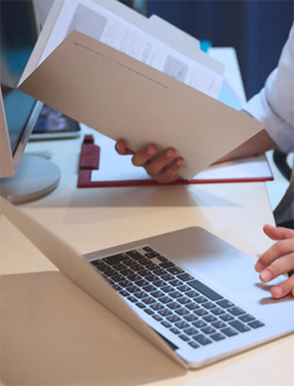 Doctor multitasking with right hand on Macbook while left hand holds open medical folder